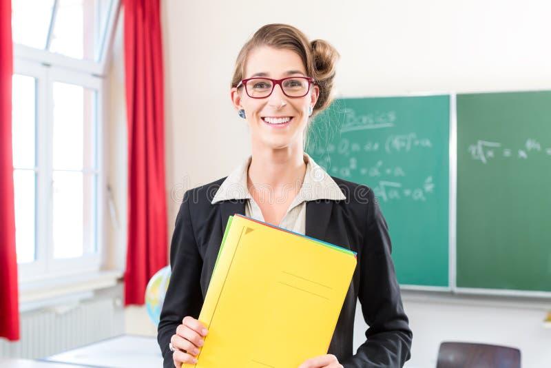 Professor que guarda o dobrador na escola na frente de uma classe fotografia de stock