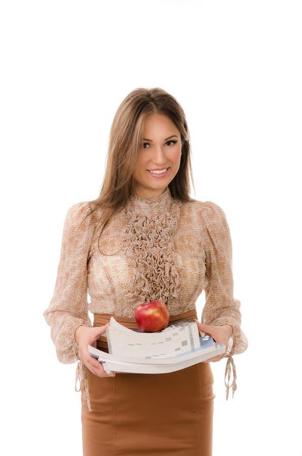 Professor que leva uma pilha de livros com uma maçã na parte superior imagem de stock