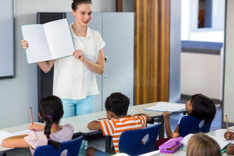 Professor que mostra o livro com crianças fotos de stock royalty free