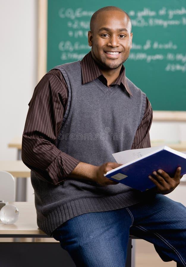 Professor que senta-se na mesa com livro de texto fotos de stock