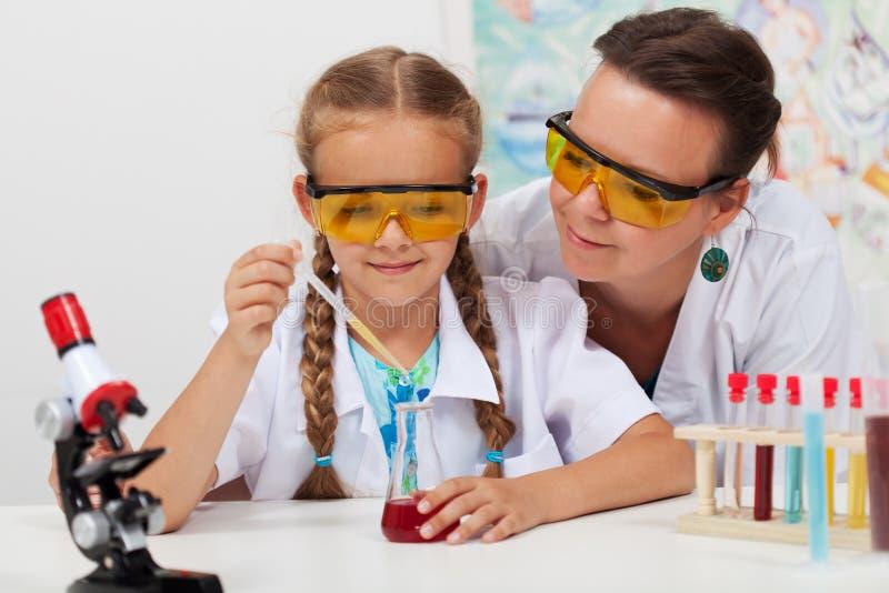 Professor que vigia a experiência química na classe da ciência imagem de stock