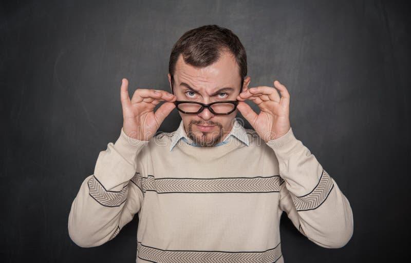 Professor restrito considerável nos monóculos que olham o no quadro-negro imagem de stock