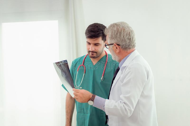 Professor senior doctor explaining case study to assistance abou royalty free stock image