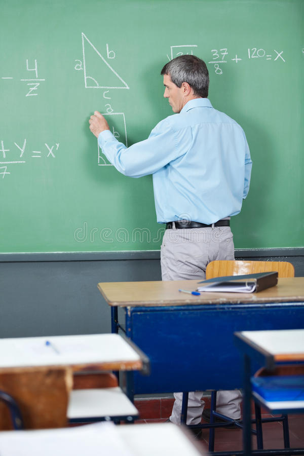 Professor Solving Mathematics On Greenboard In stock photography