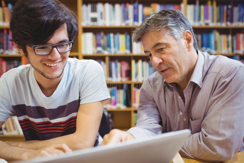 Professor som hjälper en student med studier royaltyfri foto