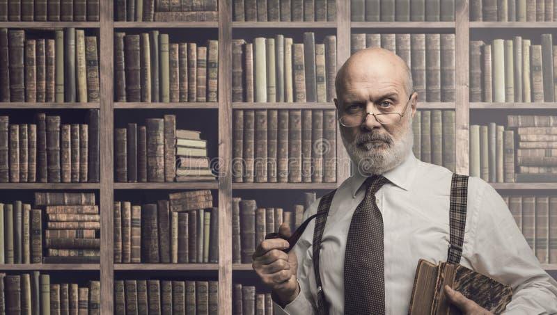 Professor som poserar i arkivet med böcker royaltyfri bild