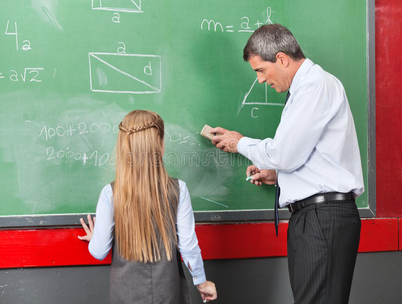 Professor Teaching Mathematics To Meisje  stock foto's