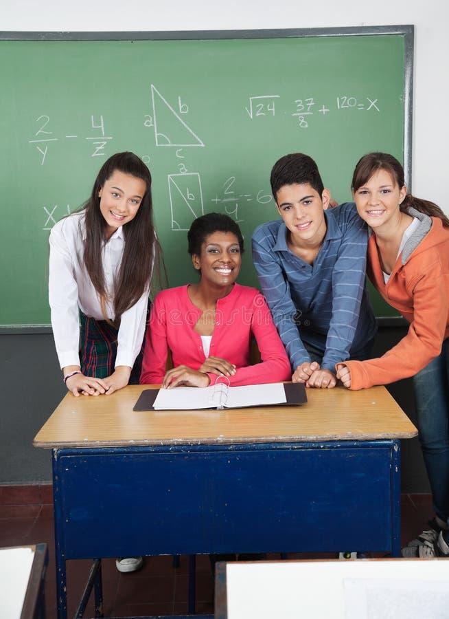 Professor With Teenage Students na mesa na sala de aula fotos de stock royalty free
