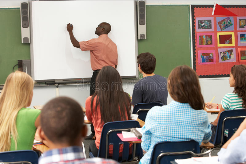 Professor Using Interactive Whiteboard durante a lição fotografia de stock