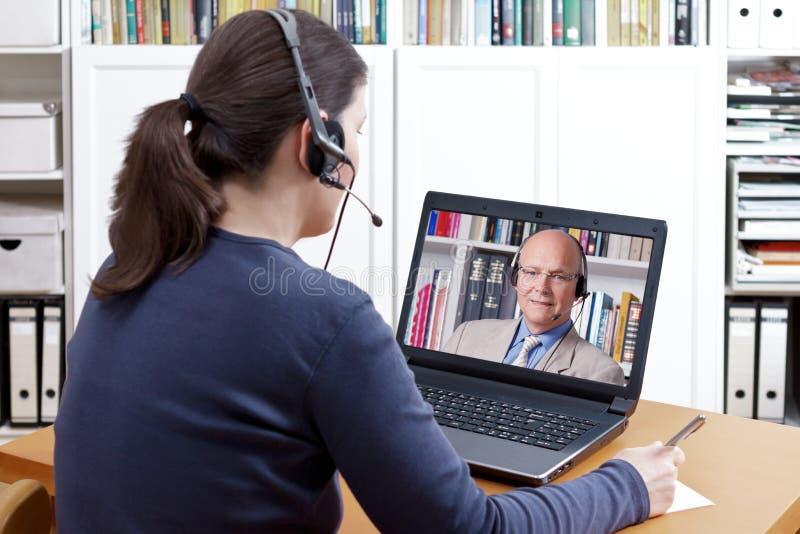 Professor video da chamada dos auriculares da mulher foto de stock