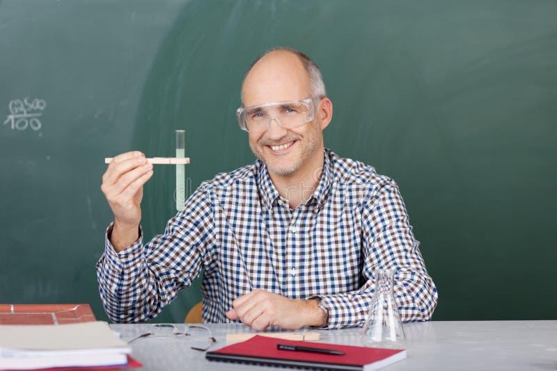 Professore di scienze di risata che sostiene una provetta immagini stock