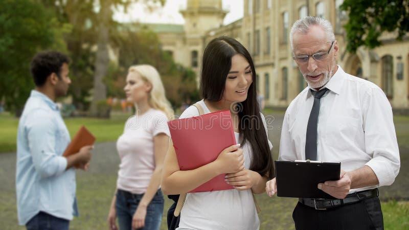 Professore maschio che discute tesi con la studentessa asiatica vicino all'università fotografie stock