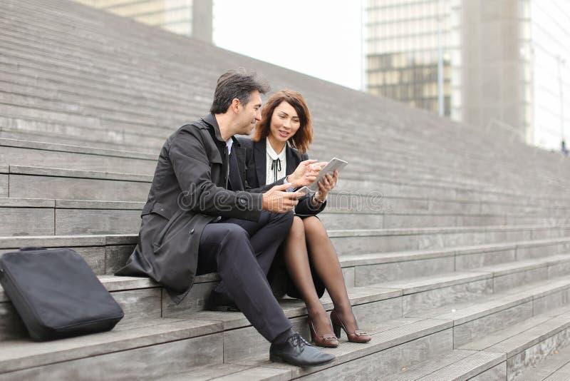 professores do negócio do casal que usam a tabuleta e o smartphon fotos de stock royalty free