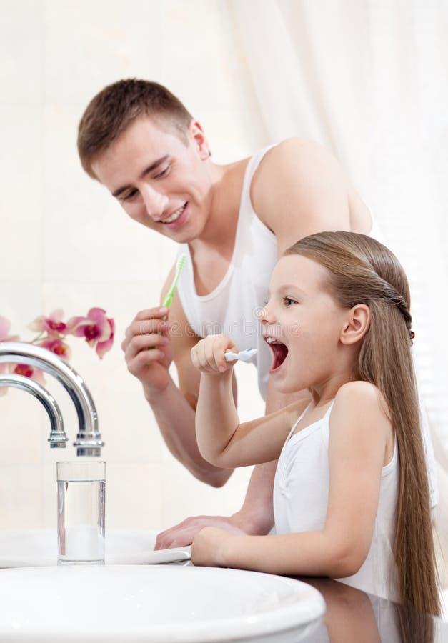 Professores do pai sua filha para limpar os dentes imagens de stock royalty free