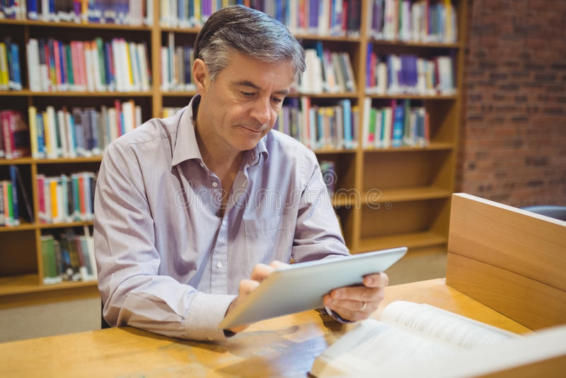 Professorsammanträde på skrivbordet genom att använda den digitala minnestavlan royaltyfria bilder