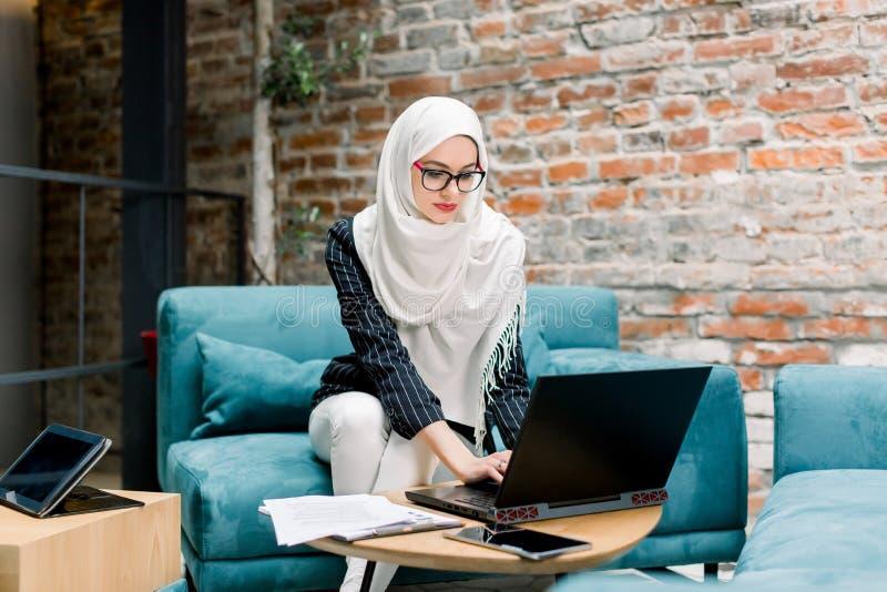 Profi-junge Muslimbusiness-Frau, die weißen Hijab trägt, Laptop-Computer benutzt, auf blauem Sofa sitzen, moderne stockbild