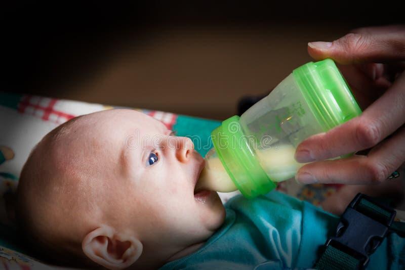 Profiel ondiepe die diepte van gebied van zuigelingsjongen met een voeden-fles wordt gevoed stock foto's