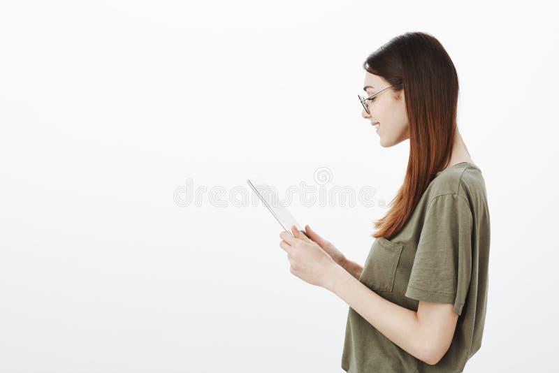 Profiel van blije aanbiddelijke volwassen vrouwelijke student in ronde glazen wordt geschoten, houdend digitale tablet en glimlac royalty-vrije stock afbeelding