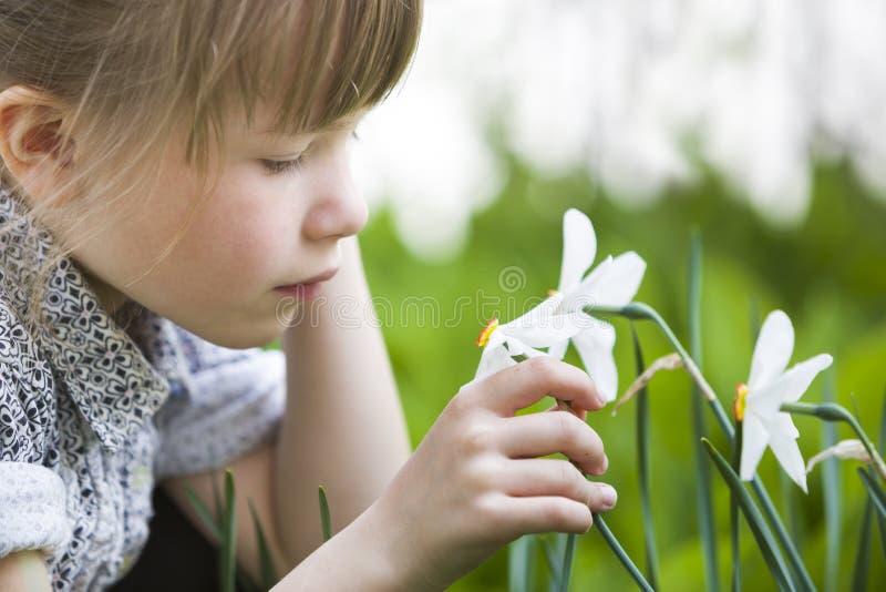 Profiel van de leuke vrij nadenkende openlucht ruikende witte gele narcis van het kindmeisje op zonnige de zomer of de lentedag royalty-vrije stock foto