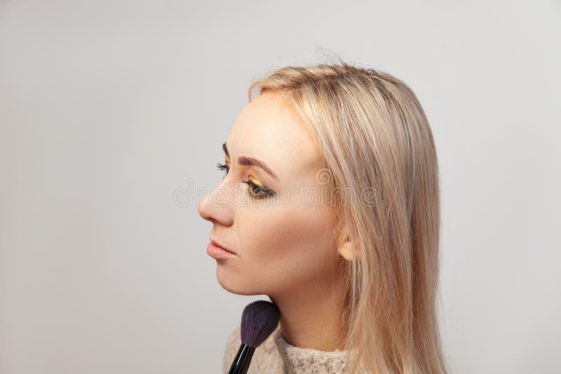 Profiel van een blondemodel met blauwe ogen op een witte achtergrond die samenstelling in de studio, de make-upkunstenaar met een stock afbeeldingen
