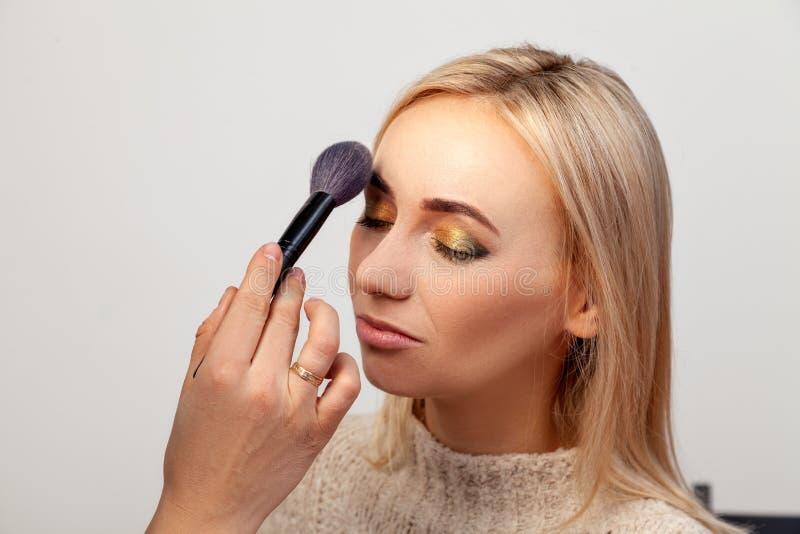 Profiel van een blondemodel met een samenstelling van het oosters-stijloog op een witte achtergrond in de studio, make-upkunstena stock afbeelding