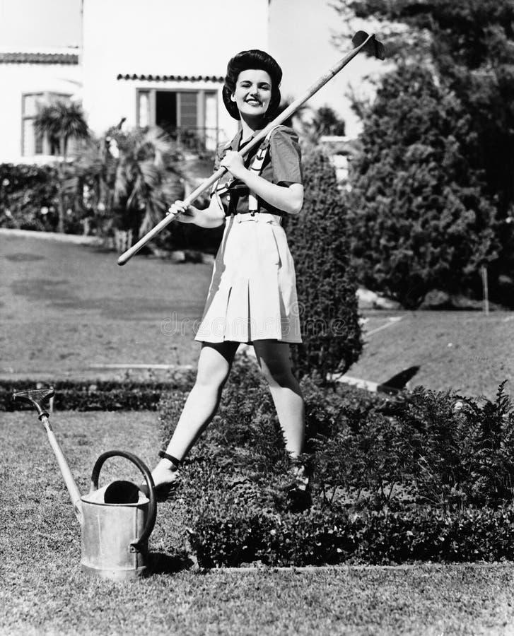Profiel van een jonge vrouw die een hark op haar schouder in een tuin dragen (Alle afgeschilderde personen langer ex leven niet e stock foto
