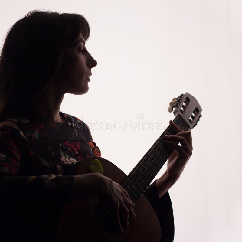 Profiel van een mooi meisje die de gitaar spelen Silhouet De ruimte van het exemplaar Een vierkant beeld royalty-vrije stock fotografie