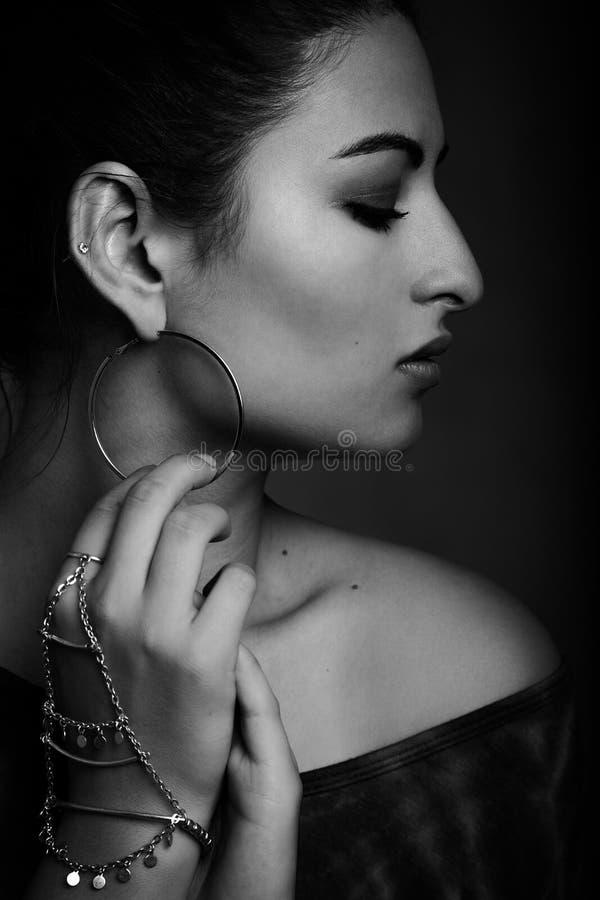 Profiel van een mooie jonge modelholding wat betreft haar oorring die wordt geschoten royalty-vrije stock afbeelding