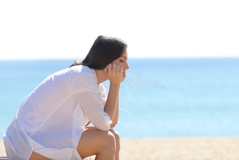 Profiel van een ongerust gemaakte vrouwenzitting op het strand stock fotografie