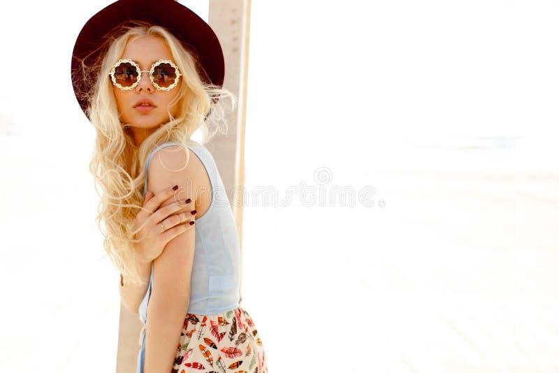 Profiel van een sexy blondemeisje met ronde oogglazen, de krullende haar en hoed van Bourgondië, dat op de overzeese achtergrond  royalty-vrije stock foto's