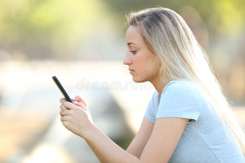Profiel van een tiener die telefooninhoud in een park controleren royalty-vrije stock afbeeldingen
