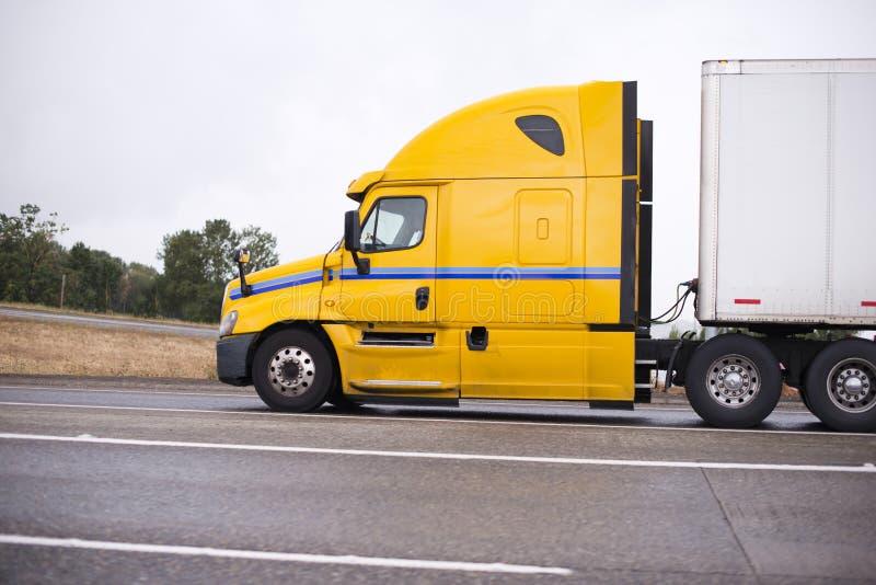 Profiel van gele grote installatie semi vrachtwagen met semi aanhangwagen die o in werking stellen royalty-vrije stock foto