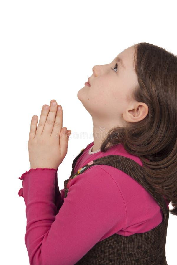 Profiel van het mooie meisje omhoog bidden en het kijken stock afbeelding