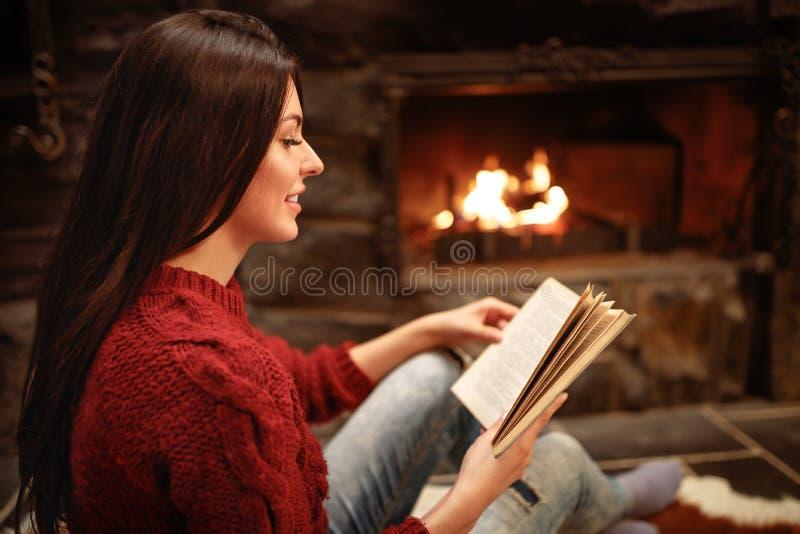 Profiel van jonge vrouw terwijl het lezen van boek stock fotografie