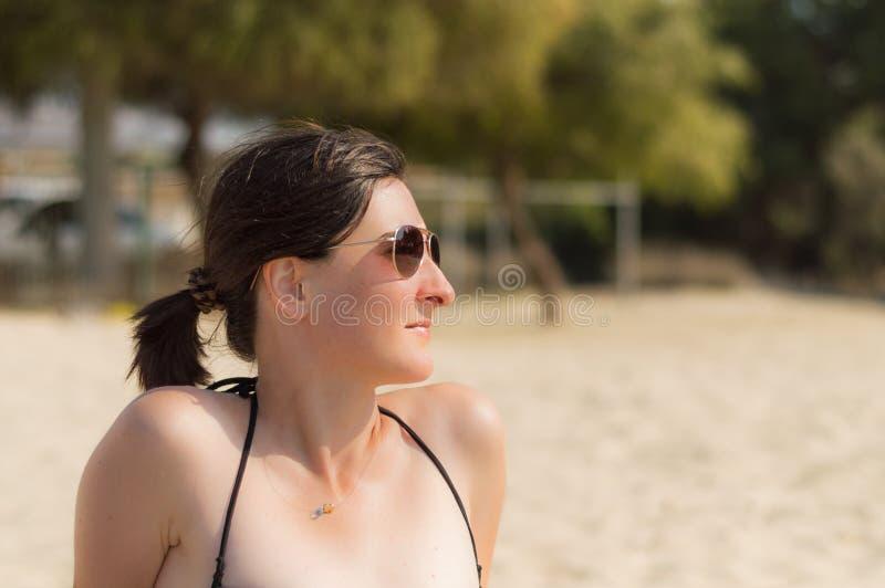 Profiel van mooie jonge gelukkige Kaukasische vrouw die met zonnebril van de zon genieten bij het strand stock foto's
