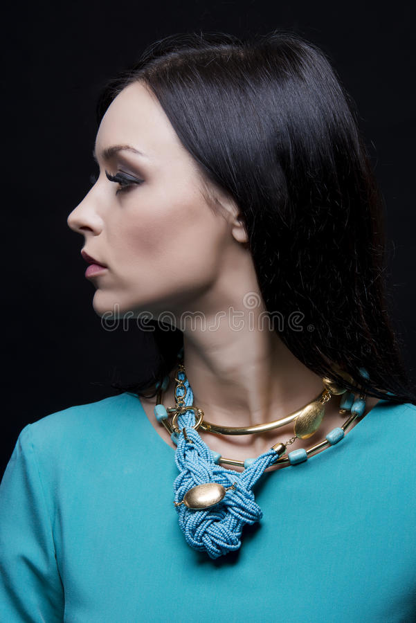 Profiel van mooie modieuze vrouw die cyaankleren en juwelen dragen stock foto