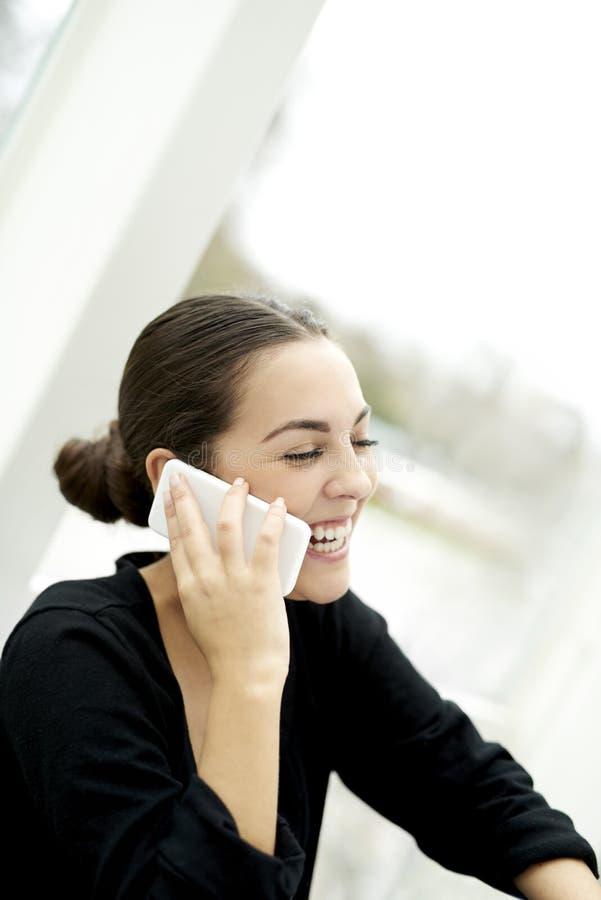 Profiel van vrouw het lachen op telefoon stock afbeeldingen