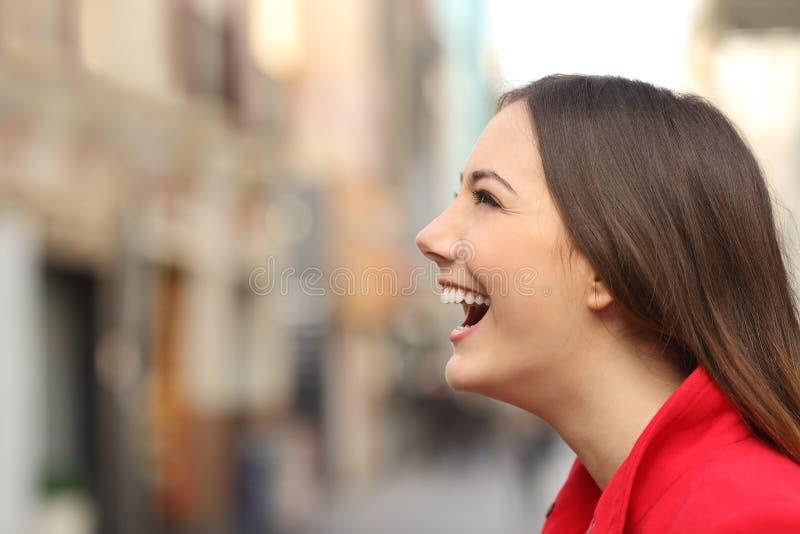 Profiel van vrouwengezicht lachen gelukkig in de straat stock afbeelding