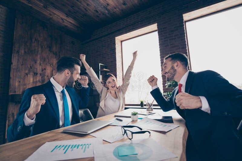 Profiel zijaanzicht van drie elegante elegante modieuze in mooie knappe vrolijke managers die verheugende verkoop vieren stock fotografie