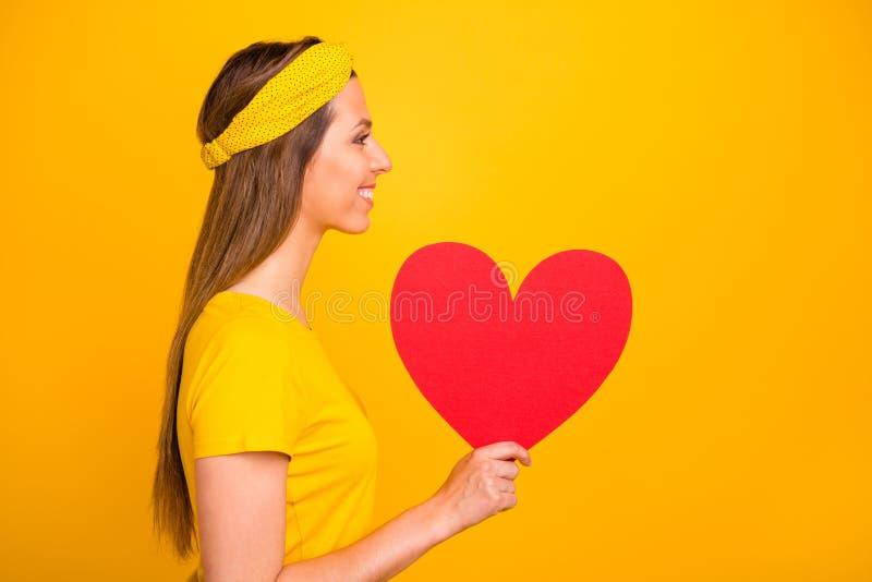 Profiel zijfoto van spontaan millennial holdings groot hart voor valentijnskaartdag die met het richten van over geïsoleerde glim royalty-vrije stock foto's