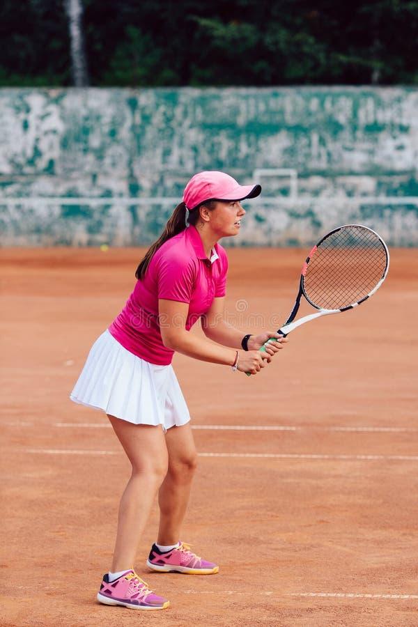 Profielbeeld van jonge professionele sportieve vrouw in roze t-shirt en witte rok, die tennis speelt en wacht op royalty-vrije stock foto's