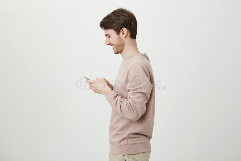 Profielfoto van aantrekkelijk mannetje met in kapsel en varkenshaarholdingssmartphone en het lachen over iets ziet hij royalty-vrije stock fotografie