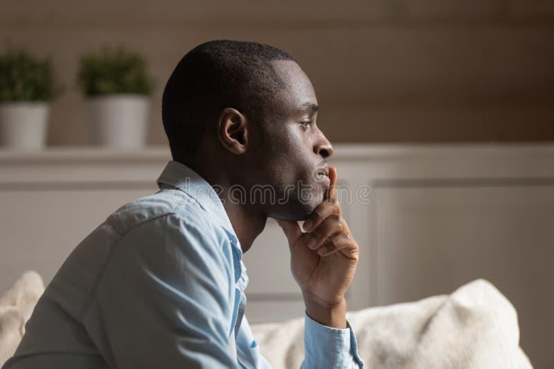 Profielgezicht van droevige Afrikaanse kerel die binnen denken royalty-vrije stock foto