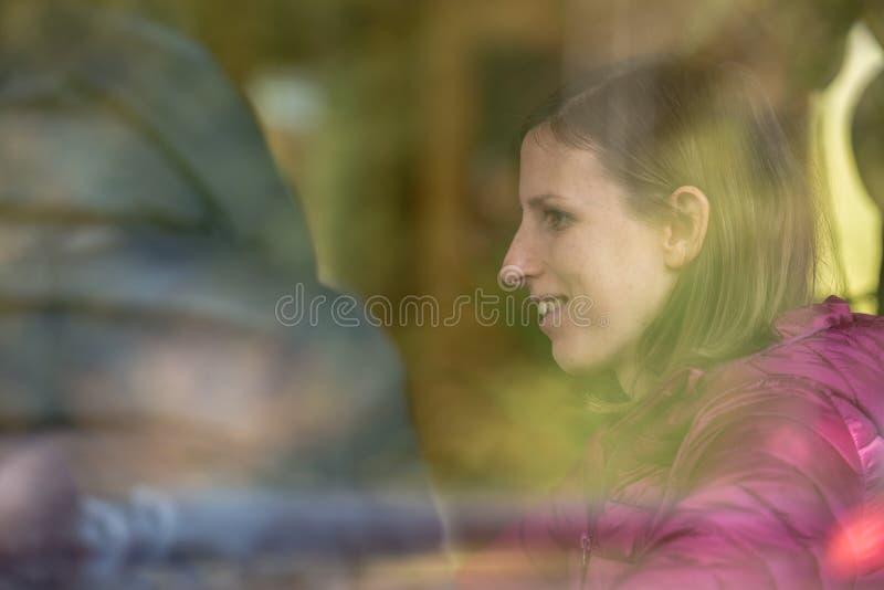 Profielmening van een het glimlachen jonge vrouwenzitting binnen een sh koffie stock afbeeldingen