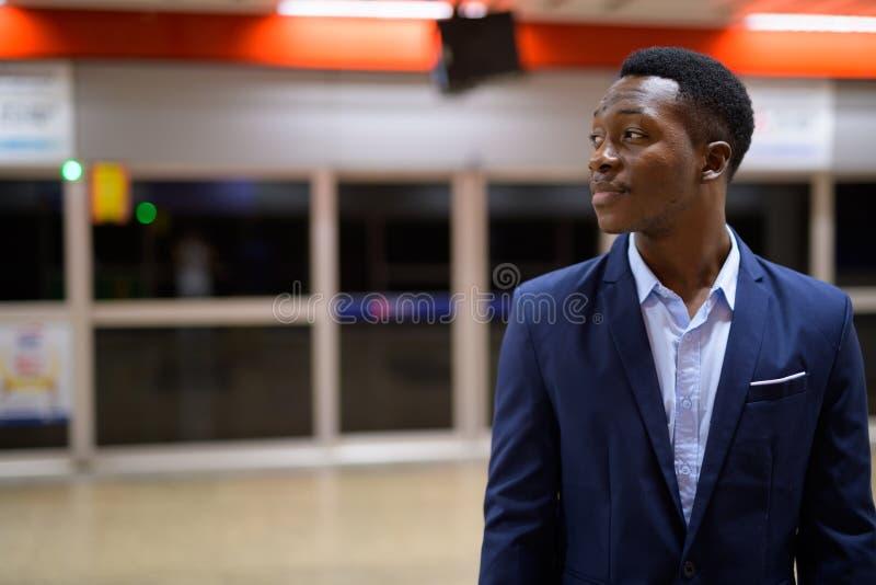 Profielmening van het jonge Afrikaanse zakenman wachten in het metrostation stock fotografie