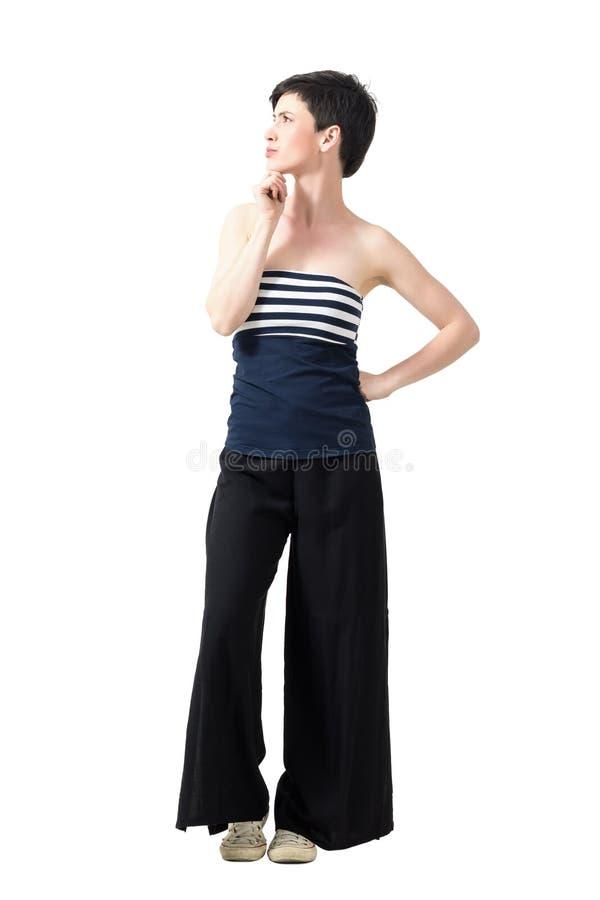 Profielmening van het jonge korte haar mooie vrouw denken en het kijken omhoog met hand op kin stock foto's