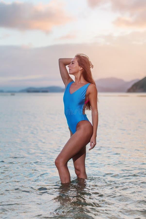 Profielmening van mooi vrouwelijk model in blauw zwempak die zich in overzees bij zonsondergang bevinden stock foto