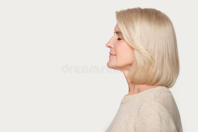 Profielmening verouderde vrouw die zich op grijze studioachtergrond afzijdig houden stock fotografie