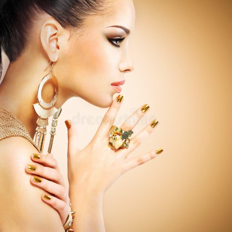 Profielportret van de maniervrouw met mooie gouden mani stock afbeelding