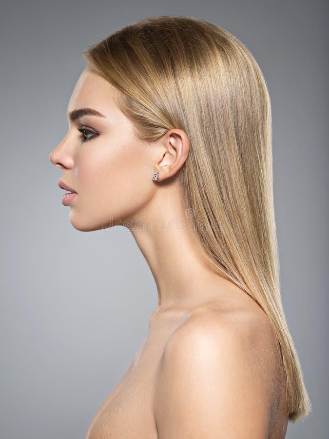 Profielportret van een vrouw met lang licht recht haar stock afbeelding